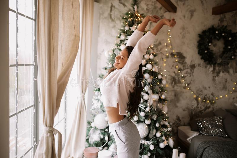 Charming girl dressed in white sweater and pants stands next to the New Year tree in front of the window and stretches. Up  in a cozy decorated room  with New royalty free stock photography