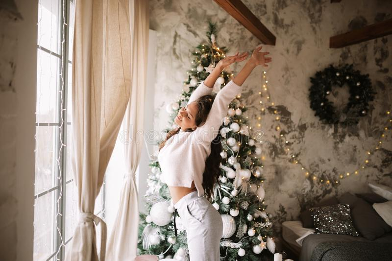 Charming girl dressed in white sweater and pants stands next to the New Year tree in front of the window and stretches. Up  in a cozy decorated room  with New royalty free stock image