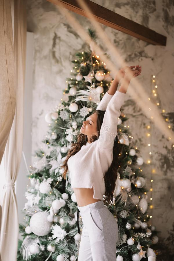 Charming girl dressed in white sweater and pants stands next to the New Year tree in front of the window and stretches. Up  in a cozy decorated room royalty free stock photos