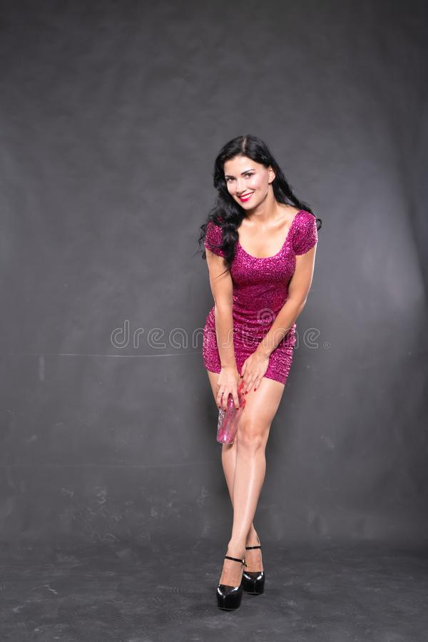 Charming girl in fuchsia sequin dress with water glass on black background in Studio. Alone stock images