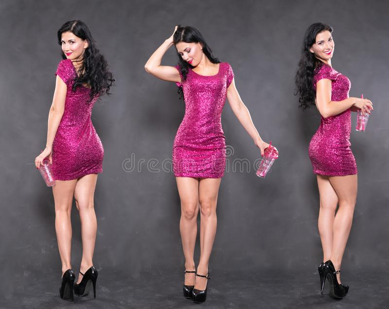 Charming girl in fuchsia sequin dress with water glass on black background in Studio. Alone stock image
