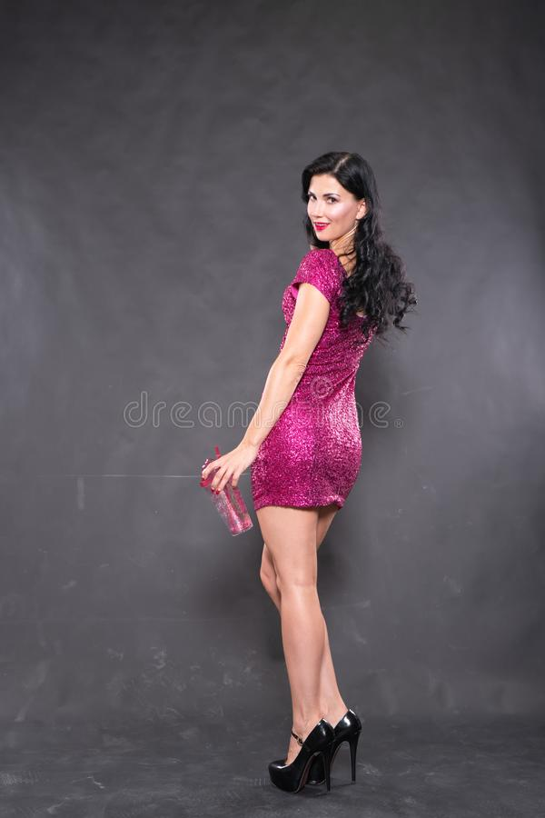 Charming girl in fuchsia sequin dress with water glass on black background in Studio. Alone royalty free stock image