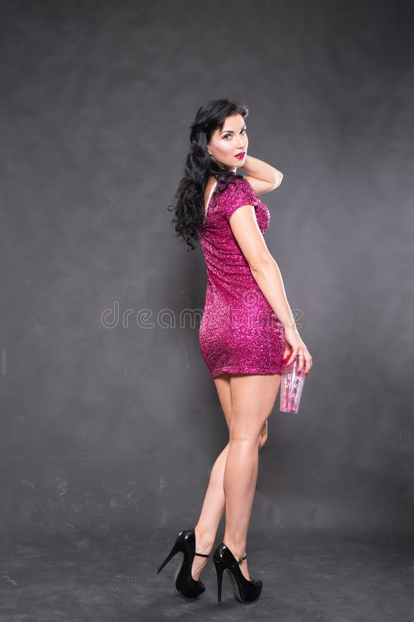 Charming girl in fuchsia sequin dress with water glass on black background in Studio. Alone stock photos