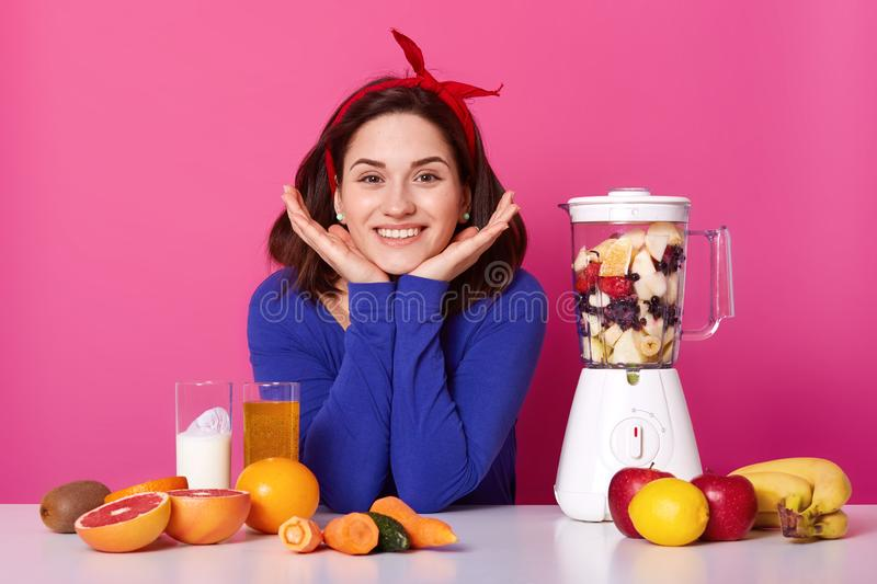 Charming girl, holds hands under chin, wears red headband, blue jumper, uses food processor for making fresh smoothie for. Breackfast, different fruit and stock photography