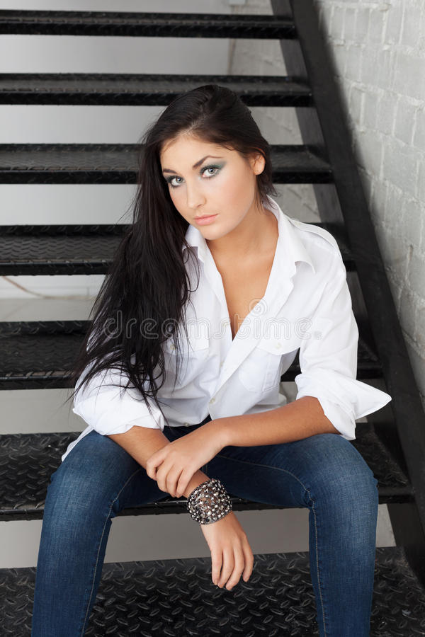 Simple beauty. Charming girl in jeans and shirt sitting on a stairs stock image