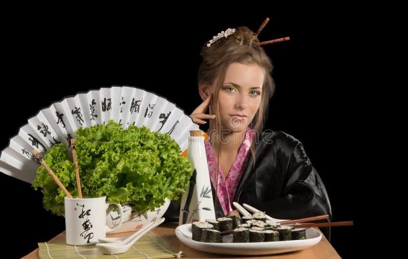 Charming Girl In Kimono Eating Sushi Royalty Free Stock