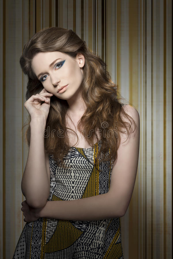 Charming girl with lovely dress. Charming woman with long natural hair, cute blue make-up and lovely vintage dress. Looking in camera stock image