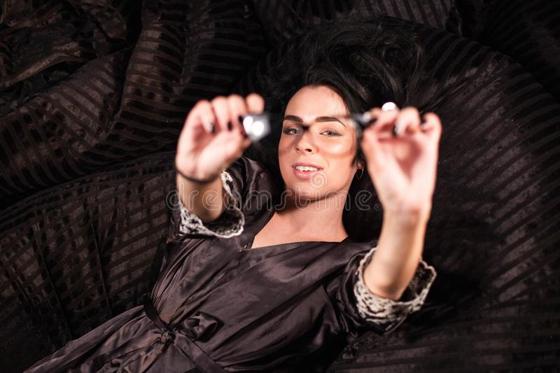 Charming girl lying with outstretched hands. WOman showing her glasses. Charming girl lying with outstretched hands. WOman showing her glasses royalty free stock photos