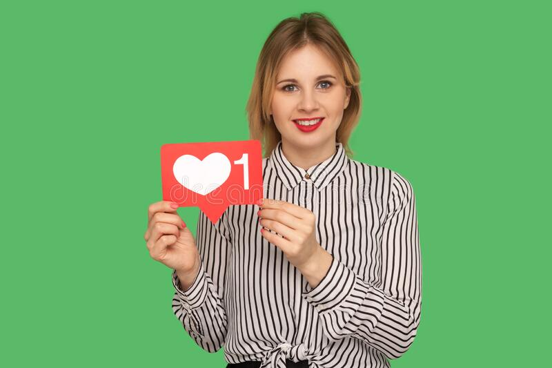 Charming girl with red lips in glamour striped blouse holding social media heart Like icon and smiling to camera. Recommending to follow and love content royalty free stock photos