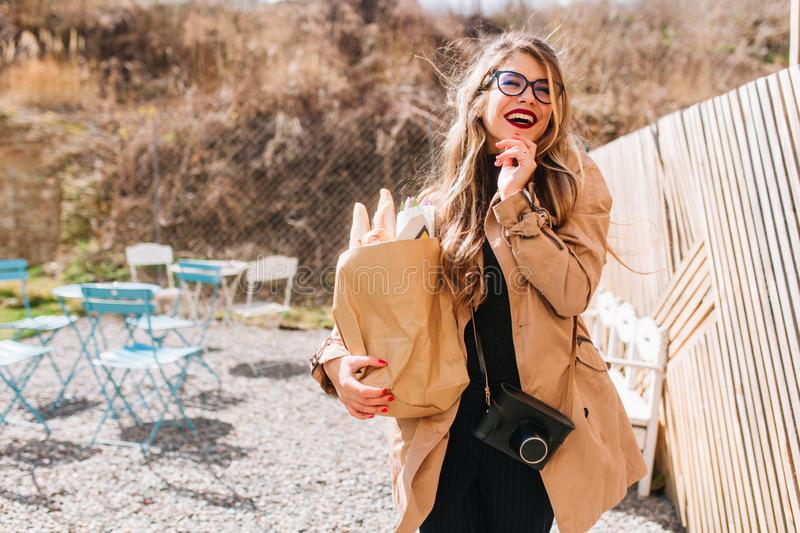Charming girl in retro outfit holding paper bag from grocery and posing with flirtatious smile. Stylish young woman in royalty free stock image