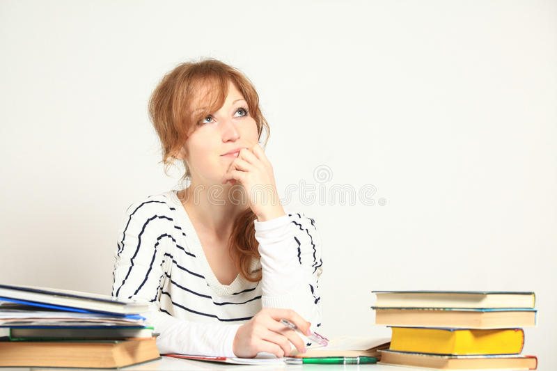Charming girl sitting at table with books stock images