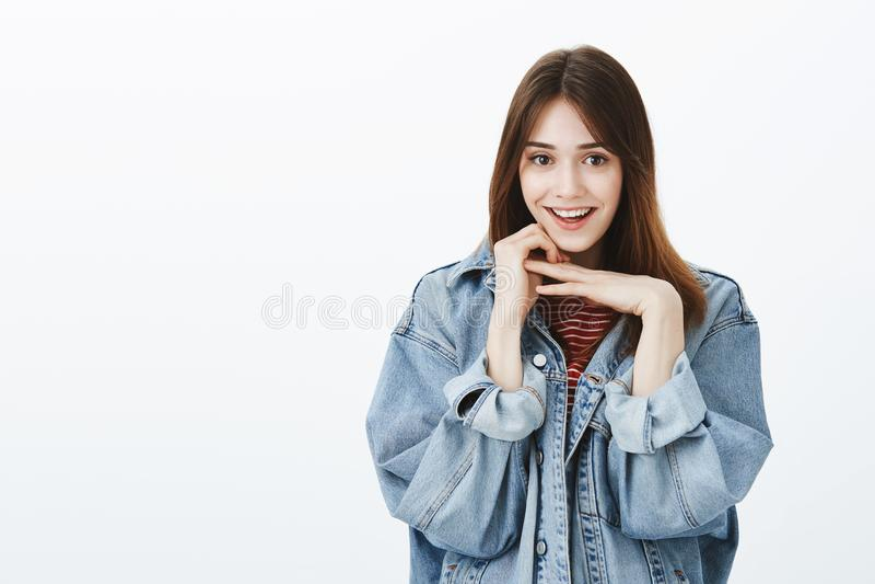 Charming girlfriend listening curiously interesting story. Portrait of pretty happy brunette in stylish denim jacket stock photography