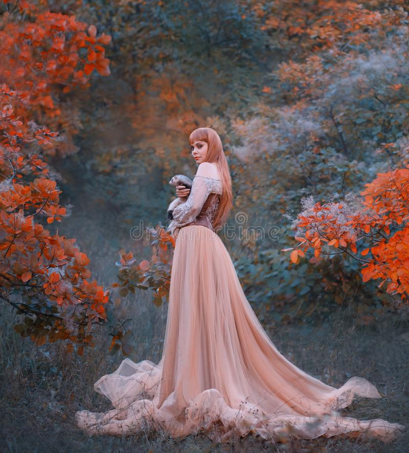 Charming gorgeous girl with fiery red hair stands alone in forest in long light elegant dress with leather corset and stock photography