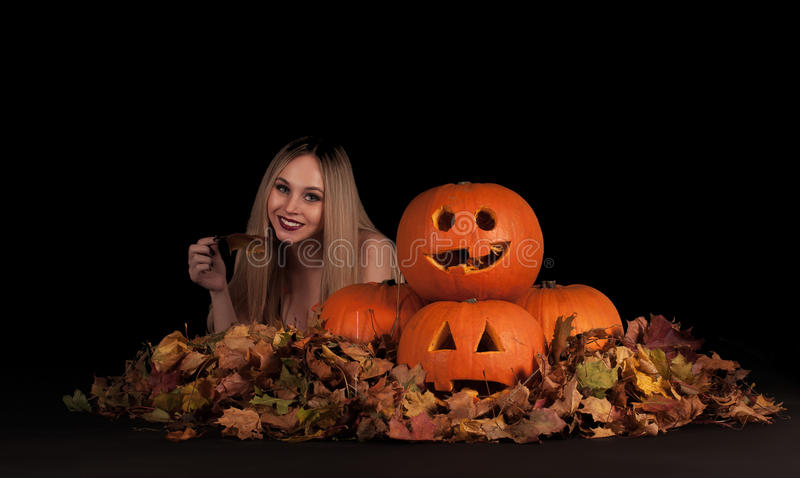 Charming halloween witch with funny pumpkins. And leaves over black background royalty free stock image