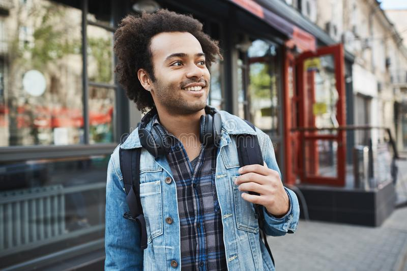 Charming handsome african-american male with bristle and afro haircut looking aside while holding backpack and strolling. In city. DJ heading to club to perform stock photography