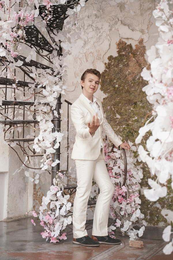 Charming handsome Caucasian young man in a white business suit, jacket and trousers, posing against a pink Sakura. Fashion trendy male teenager in stylish white stock image