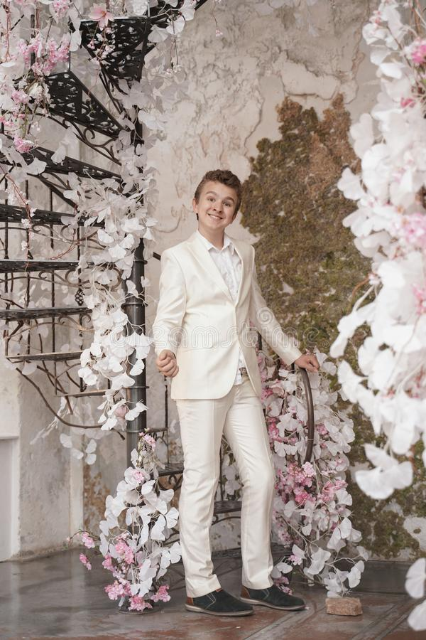 Charming handsome Caucasian young man in a white business suit, jacket and trousers, posing against a pink Sakura. Fashion trendy male teenager in stylish white royalty free stock photo
