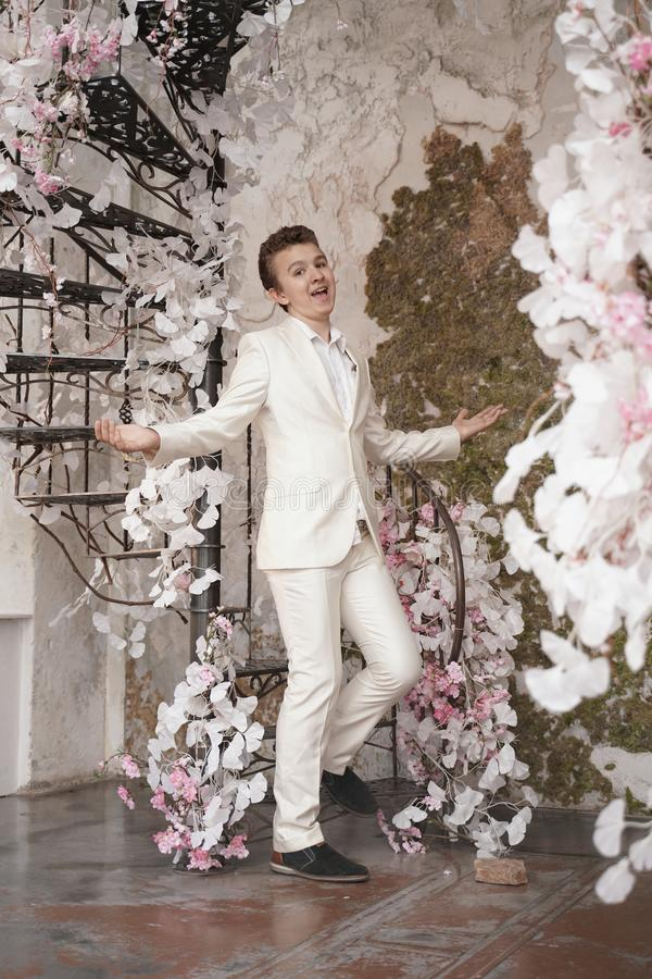 Charming handsome Caucasian young man in a white business suit, jacket and trousers, posing against a pink Sakura. Fashion trendy male teenager in stylish white royalty free stock photos