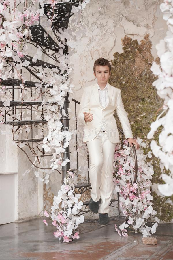 Charming handsome Caucasian young man in a white business suit, jacket and trousers, posing against a pink Sakura. Fashion trendy male teenager in stylish white royalty free stock image