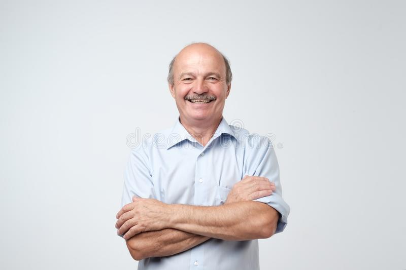 Charming handsome senior man in casual blue shirt keeping arms crossed and smiling royalty free stock photography