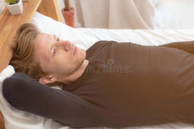 Charming handsome young guy thinking something about his future life on bed at bedroom. Attractive handsome man gets stressed. Because he loses his job and does stock photography