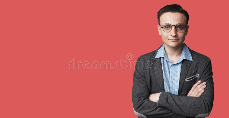 Charming handsome young man in casual wear keeping arms crossed stock images