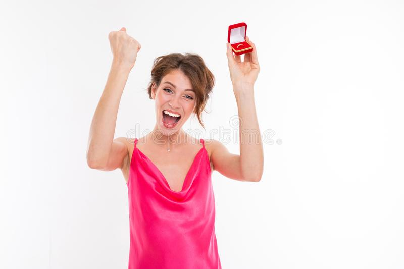 Charming happy girl in a pink dress with a box with a wedding ring says yes on a white background stock image