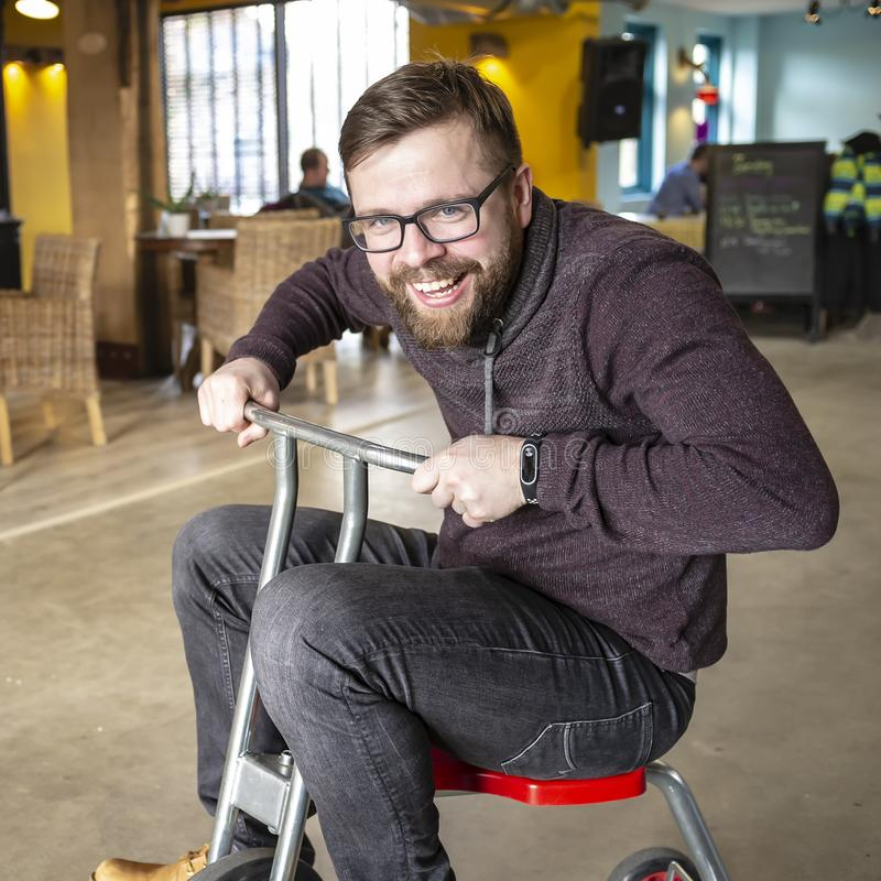 Charming, happy, smiling father with a beard and glasses, he took from his son a children`s bicycle and happily rolls around in a stock photography