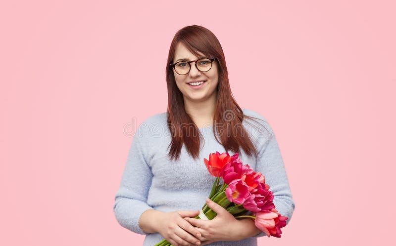 Beautiful plump woman with tulips stock image