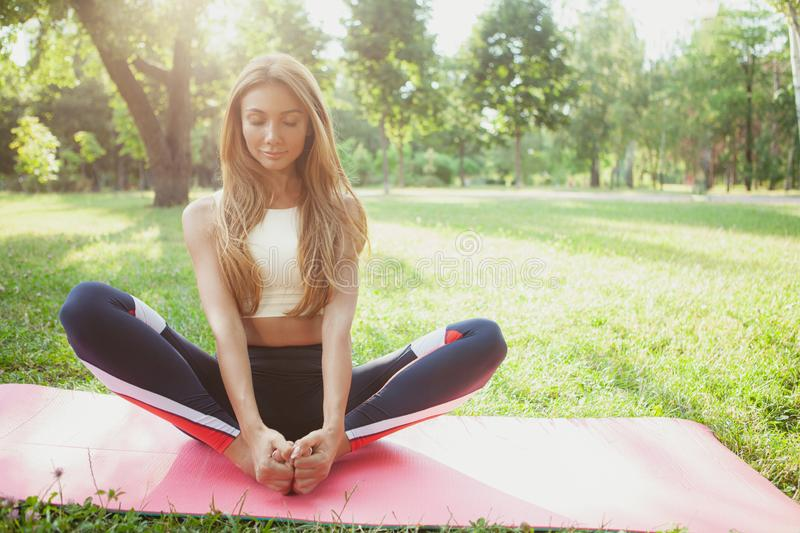 Gorgeous athletic woman doing yoga at the park royalty free stock photos