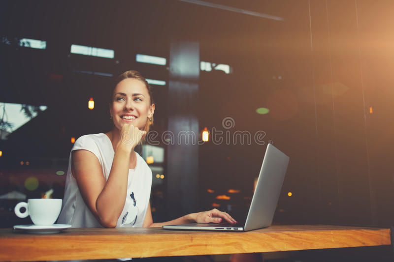 Charming happy woman student using laptop computer to prepare for the course work. Young female with cute smile sitting with portable net-book in modern coffee