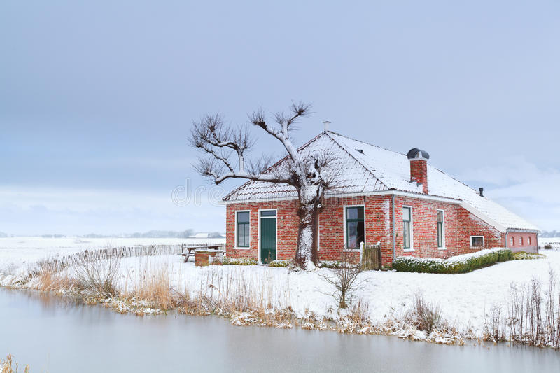 Charming house in winter snow by river stock image