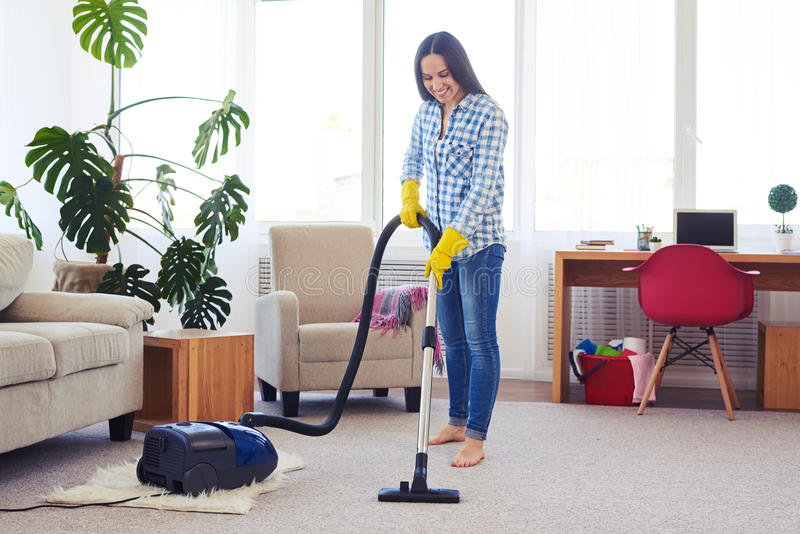 Charming housewife cleaning with vacuum cleaner carpet. Wide shot of charming housewife cleaning with vacuum cleaner carpet royalty free stock photography
