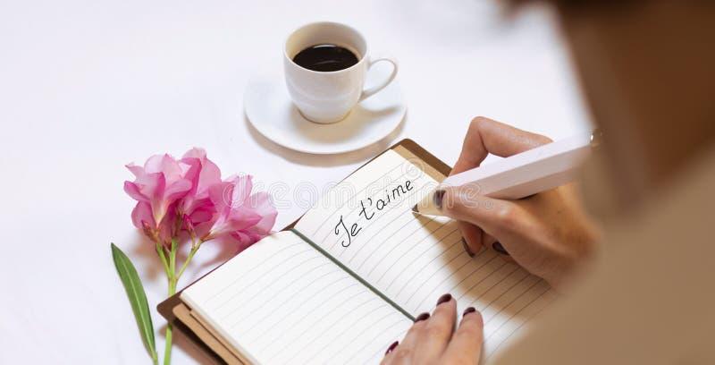 Charming Italian escribe una nota de amor para su esposo y lo invita a una cita. `Je t`aime´ - Te amo imagen de archivo libre de regalías
