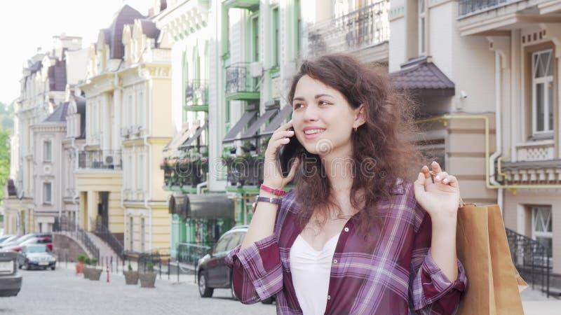 Charming joven mujer habla por teléfono en la calle de la ciudad con bolsas de compras foto de archivo libre de regalías