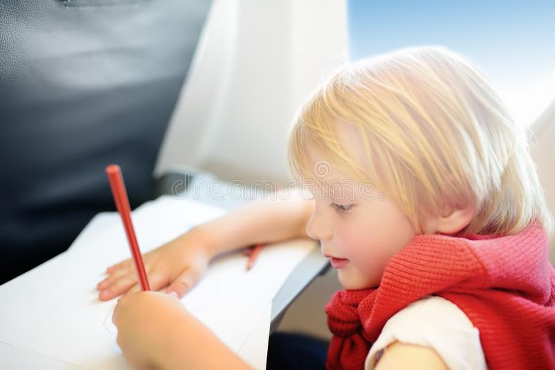 Charming kid traveling by an airplane. Joyful little boy sitting by aircraft window during the flight. Child drawing picture royalty free stock image