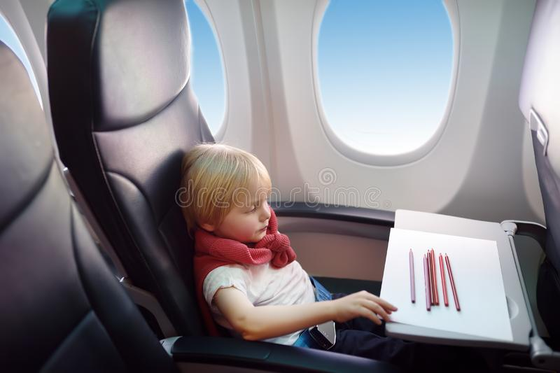 Charming kid traveling by an airplane. Joyful little boy sitting by aircraft window during the flight. Child drawing picture royalty free stock photo