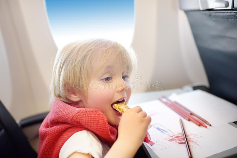 Charming kid traveling by an airplane. Joyful little boy sitting by aircraft window during the flight. Child drawing picture and stock photo