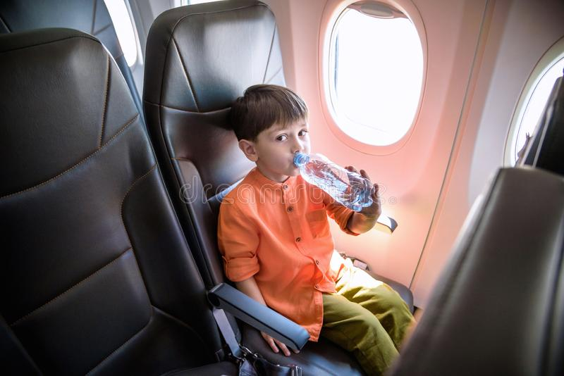 Charming kid traveling by an airplane. Little boy drinking water during the flight. Air travel with little kids.  stock images