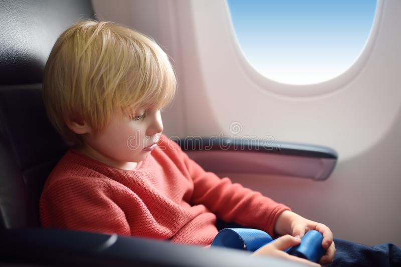 Charming kid traveling by an airplane. Little boy sitting by aircraft window during the flight. Air travel with kids royalty free stock photography