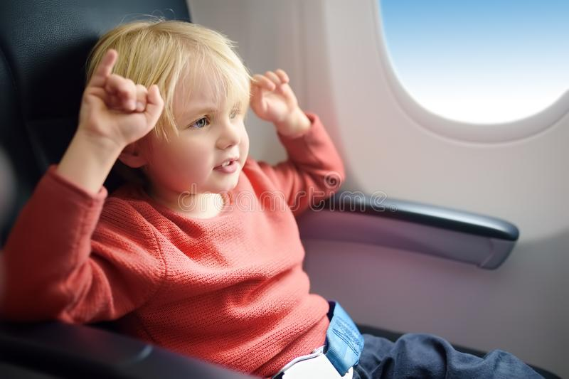 Charming kid traveling by an airplane. Little boy sitting by aircraft window during the flight. Air travel with kids royalty free stock image