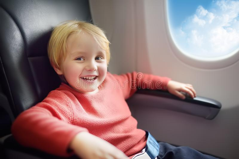 Charming kid traveling by an airplane. Little boy sitting by aircraft window during the flight. Air travel with kids stock photography