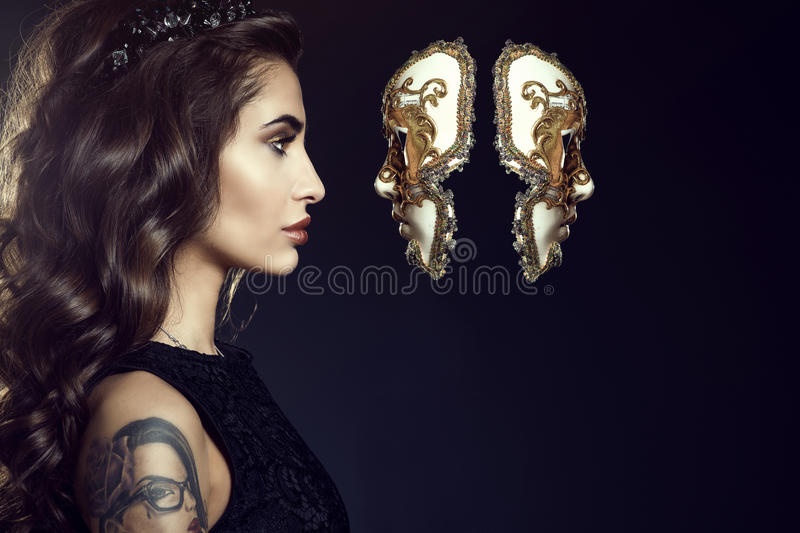 Charming lady with dark wavy silky hair wearing jewel crown and looking in the face of Venetian mask hanging in the air stock images