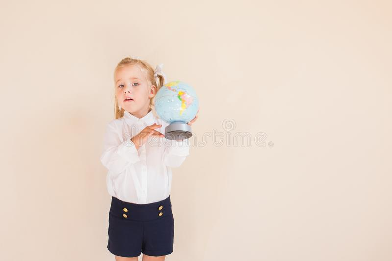 Charming little blonde girl in school uniform is holding a globe, looking at camera, standing on neutral background. Copyspace stock photography