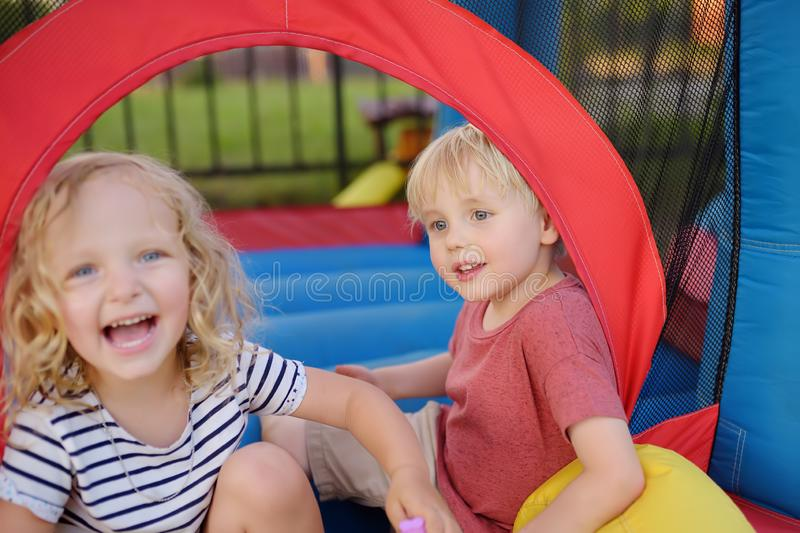 Charming little boy and girl having fun in leisure center for kids. Child sport activity on outdoor playground royalty free stock photography