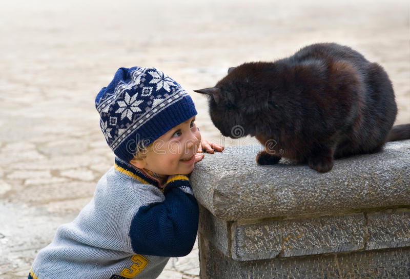 Charming little boy playing with a black cat stock photo