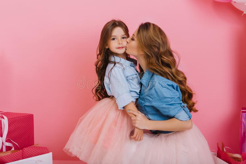 Charming little brunette girl spending time with her young beautiful mom at birthday party. Adorable curly woman wearing royalty free stock photos