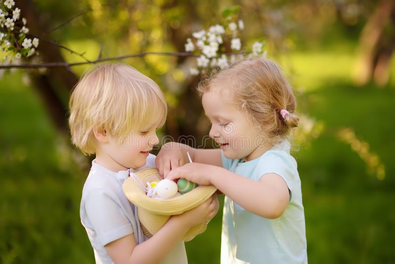 Charming little children hunts for painted eggs in spring park on Easter day. Traditional easter festival outdoors stock images
