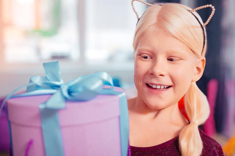 Charming little female having birthday party at home. It is surprise. Beautiful blonde girl expressing positivity while staring at gift box stock photos