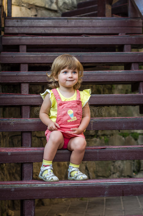 Charming little girl baby sitting on the wooden stairs in a beautiful dress while walking in Lviv royalty free stock photos